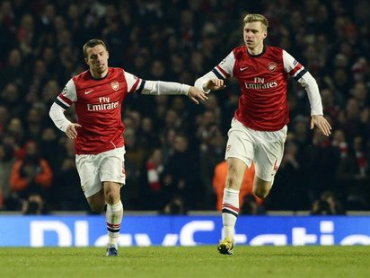 Arsenal's Lukas Podolski (L) celebrates with teammate Per Mertesacker after scoring against Bayern Munich during their Champions League socc