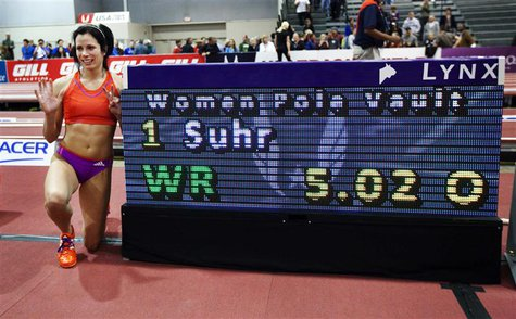 Jenn Suhr poses next to the score board after setting a new women's indoor pole vault world record of 5.02 metres (16 feet 5 1/2 inches) at