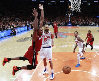 Miami Heat center Chris Bosh reacts after scoring against New York Knicks center Tyson Chandler (6) and guard J.R. Smith (R) in the fourth q
