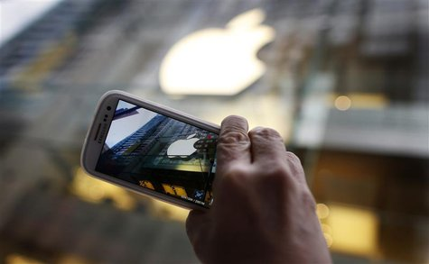A passerby photographs an Apple store logo with his Samsung Galaxy phone in central Sydney in this September 21, 2012, file photo. REUTERS/T