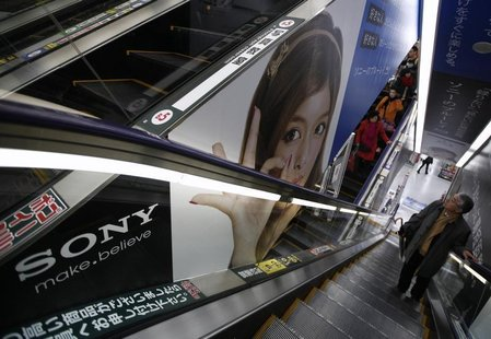 A man riding an escalator passes an advertisement of Sony Corp. at an electronic store in Tokyo February 6, 2013. REUTERS/Shohei Miyano