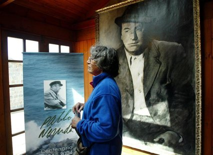 A woman looks at a painting of Chilean poet and Nobel laureate Pablo Neruda during a ceremony the 30th anniversary of his death, in Isla Neg