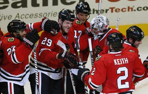Chicago Blackhawks' goalie Ray Emery (3rd R) is surrounded by teammates after his team's win over the Vancouver Canucks in their NHL hockey