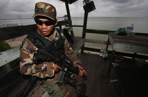 A member of the Royal Malaysian Navy's Naval Special Warfare Forces guards the beach near an area where armed men are holding off, in Felda