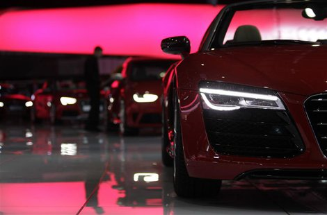 A staff cleans cars on the Audi stand ahead of the 83rd Geneva Car Show at the Palexpo Arena in Geneva March 4, 2013. The Geneva Motor Show