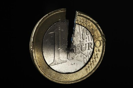 A damaged one Euro coin being held in a vise is pictured in this photo illustration taken in Warsaw September 13, 2012. Picture take Septemb