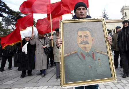 People carry red flags and a portrait of the late Soviet leader Josef Stalin during a ceremony to mark the 60th anniversary of his death in