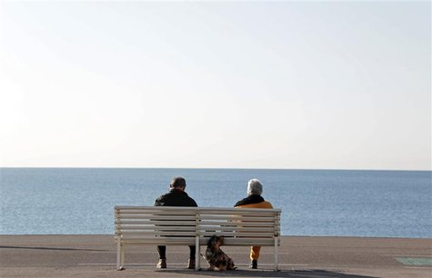 Elderly people sit on a bench to take in the sun with their dog along the Promenade Des Anglais in Nice February 19, 2013. France's Presiden