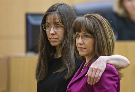 Jodi Arias puts her arm around defense attorney Jennifer Willmott (R), after being asked to demonstrate how she had her arm around her siste