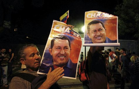 Supporters of Venezuela's President Hugo Chavez show pictures of him as they react to the announcement of his death outside the Venezuelan E