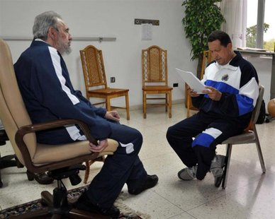 Former Cuban leader Fidel Castro (L) looks on as Venezuela's President Hugo Chavez reads a document in Havana in this July 3, 2011 file hand