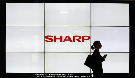 A woman walks past the Sharp Corp's Logo at a train station in Tokyo March 6, 2013. Samsung Electronics Co is set to invest $110 million in