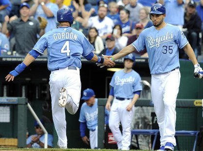 Kansas City Royals Alex Gordon is congratulated by Eric Hosmer (R) after scoring on a Billy Butler double in the first inning against the Ne