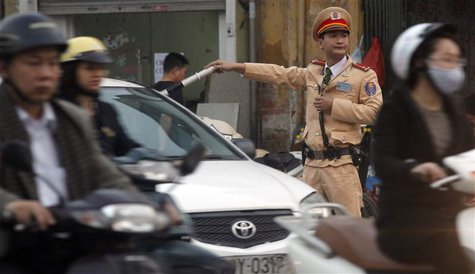A policeman directs traffic on a street in Hanoi March 6, 2013. REUTERS/Kham