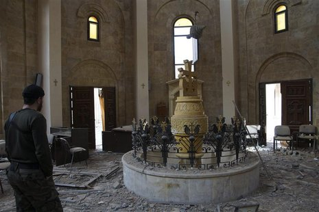 A member of the Free Syrian Army stands inside an Armenian church in Deir al-zor ,March 5, 2013. Picture taken March 5, 2013. REUTERS/Khalil