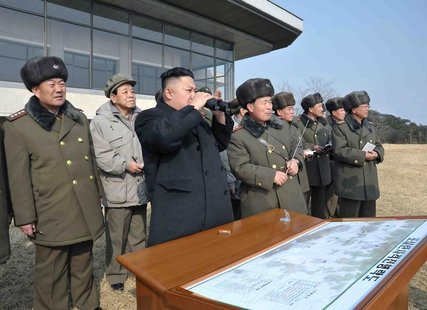 North Korean leader Kim Jong-Un (C) inspects an artillery firing drill of the Korean People's Army units in an undisclosed location in this