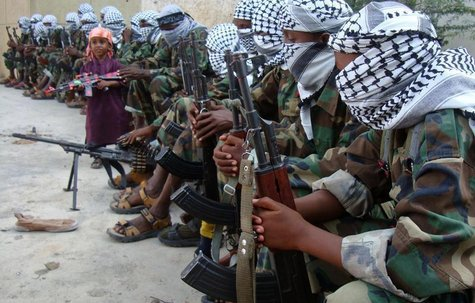 A boy carrying a toy gun stands near members of Somalia's hardline al Shabaab rebel group after attending Eid al-Adha prayers inside a footb