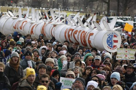 Demonstrators carry a replica of a pipeline during a march against the Keystone XL pipeline in Washington, February 17, 2013. REUTERS/Richar