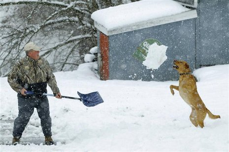 Bill Groves plays with his dog Red while shovelling snow during a massive blizzard near Mt. Jackson, Virginia March 6, 2013. REUTERS/Gary Ca