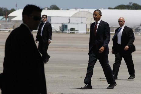 U.S. President Barack Obama walks with U.S. Secret Service agents as he prepares to board Air Force One at Hunter Army Airfield in Georgia b