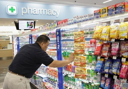A worker stocks a new Walgreens store in Chicago January 9, 2012. REUTERS/John Gress