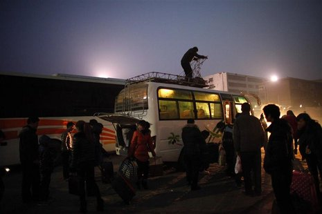 People arrive at a city bus station in the town of Zhoukou, Henan Province for a trip to work in a shoes factory at coastal industrial area