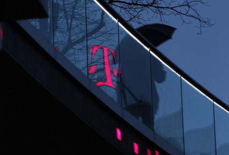 A man walks past the logo of Deutsche Telekom AG that is reflected on glass at their headquarters, in this file photo taken in Bonn December