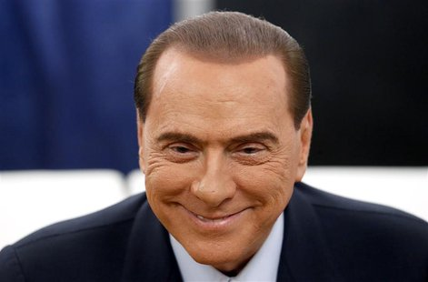 Former Prime Minister Silvio Berlusconi smiles before casting his vote at the polling station in Milan, February 24, 2013. REUTERS/Stefano R