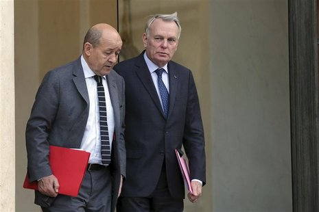 French Prime Minister Jean-Marc Ayrault (R) speaks with Defence minister Jean-Yves Le Drian at the end of a defence council at the Elysee Pa