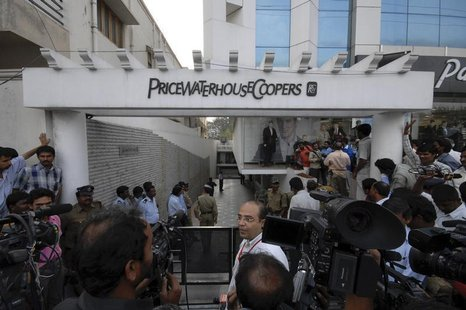 Media persons and policemen gather outside the office of PricewaterhouseCoopers (PWC), the auditors of Satyam Computers Services, in the sou