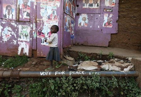 A young girl walks past election posters and a slogan calling for peace in the Kibera slum in Nairobi March 7, 2013. REUTERS/Steve Crisp