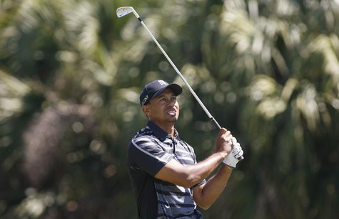 Tiger Woods of the U.S. watches his shot on the 13th tee during first round play in the 2013 WGC-Cadillac Championship PGA golf tournament i