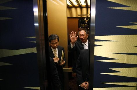 Hon Hai Precision Industry chairman and founder Terry Gou waves to the media as he gets on an elevator after a news conference in Tokyo Augu
