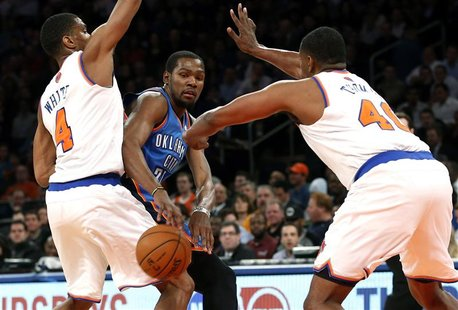 Oklahoma City Thunder forward Kevin Durant (C) passes between New York Knicks' Kurt Thomas (R) and James White during the first quarter of t