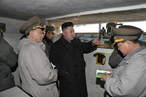 North Korean leader Kim Jong-Un (C) talks with officers at a guard post during his visit to the Jangjae Islet Defence Detachment and Mu Isle