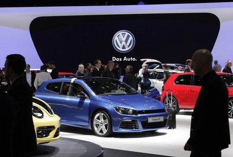Visitors stroll through cars on the Volkswagen booth during the second media day of the 83rd Geneva Car Show at the Palexpo Arena in Geneva