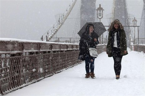 Women walk on the Brooklyn Bridge during a snowstorm in New York, March 8, 2013. A slow moving winter storm brought a combination of snow, r