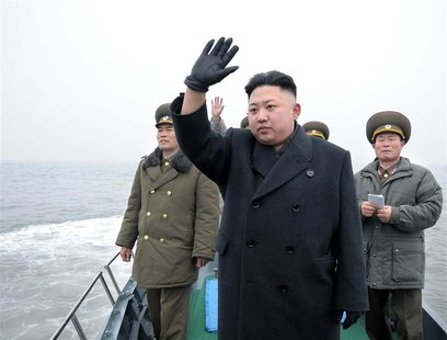 North Korean leader Kim Jong-Un (C) waves from a boat during his visit to the Jangjae Islet Defence Detachment and Mu Islet Hero Defence Det