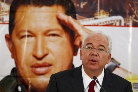 Venezuela's Energy Minister Rafael Ramirez talks to the media in front of a giant picture of Venezuela's President Hugo Chavez during a news