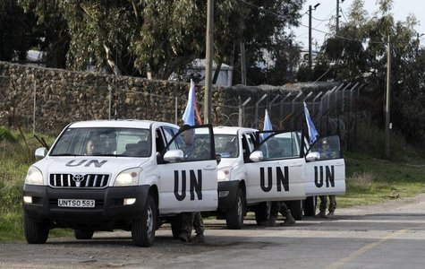 United Nations peacekeepers put on protective gear before driving through the Kuneitra border crossing between Israel and Syria, in the Isra