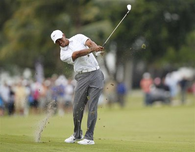 Tiger Woods hits his approach shot into the 18th green during third round play in the 2013 WGC-Cadillac Championship PGA golf tournament in