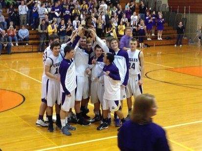 The Schoolcraft Eagles hoist their MHSAA Boys Basketball District trophy following their 66-57 win at Quincy March 8, 2013.