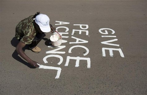 An artist known as solo7 paints a peace message on the tarmac in the Kibera slum in the Kenyan capital of Nairobi March 9, 2013. REUTERS/Kar