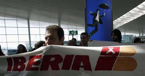 A man holds a banner during an Iberia workers strike at Terminal 1 of Barcelona's airport, March 8, 2013. REUTERS/Albert Gea