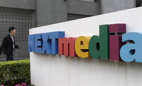 A man walks past the logo of Next Media at its headquarters in Taipei January 21, 2013. REUTERS/Pichi Chuang