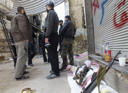 Free Syrian Army fighters stand by their weapons in the besieged area of Homs, March 9, 2013. Picture taken March 9, 2013. REUTERS/Yazan Hom