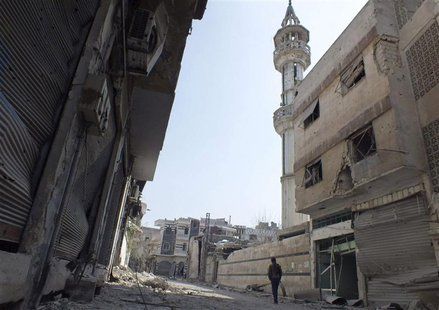 A Free Syrian Army fighter walks along a damaged street in the besieged area of Homs, March 9, 2013. Picture taken March 9, 2013. REUTERS/Ya