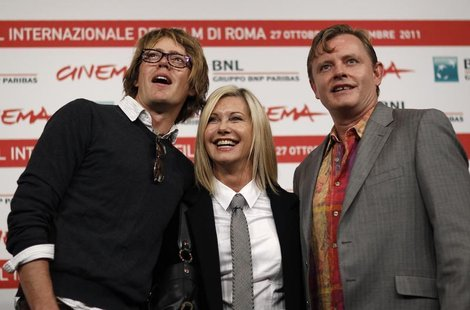 Actress Olivia Newton John (C) smiles as she poses with director Stephan Elliot (R) and actor Kris Marshall during a photocall of their movi