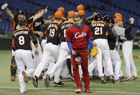Cuba's pitcher Diosdany Castillo (C) walks off the field as Netherlands' players celebrate after defeating Cuba at the World Baseball Classi