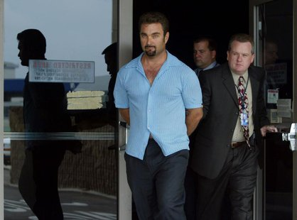 Fugitive rapist Andrew Luster (L) is led out of the U.S. Customs building by federal agents after arriving at Los Angeles International Airp